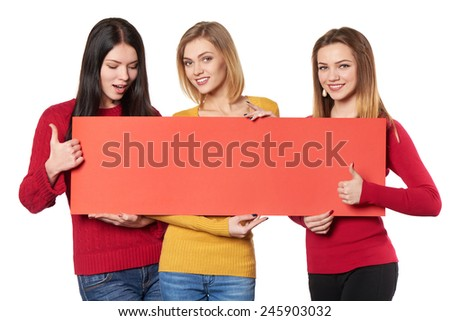 Three happy smiling girls friends holding red blank cardboard and gesturing thumbs up over white background - stock photo