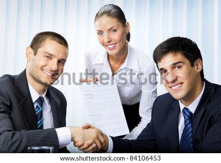 Three happy smiling successful business people handshaking with document at office - stock photo