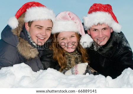 three happy smiling young people lying in snowdrift at winter outdoors over blue sky - stock photo