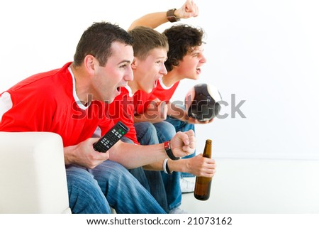 Three happy soccer fans sitting on couch and watching sport on TV. Side view. - stock photo