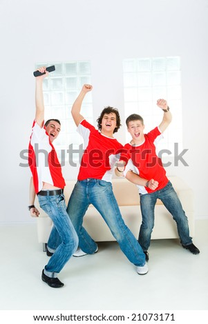Three happy sport fans get up from couch with raised hands. Front view. - stock photo