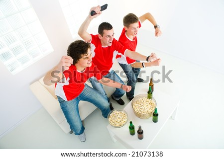 Three happy sport's fans get up from couch with raised hands. High angle view. - stock photo