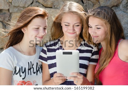 Three happy teen girl friends and tablet computer and laughing - stock photo