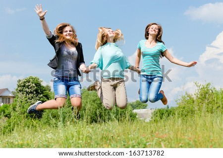 Three happy teen girls friends jumping high in blue sky on summer outdoors background