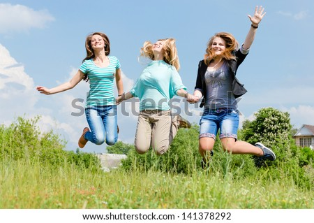 Three happy teen girls friends jumping high on green lawn against blue sky on the bright sunny day & green summer outdoors background
