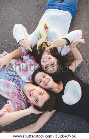 Three happy teenage friends lying together and laughing. Top view. Best friends. - stock photo