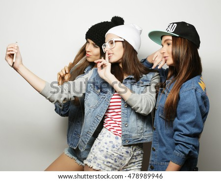 three happy teenage hipster  girls with smartphone taking selfie