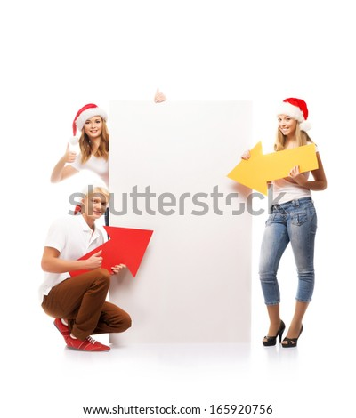 Three happy teenagers in Christmas hats pointing on a large blank banner with a red arrow