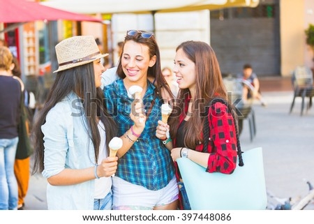Three happy women eating ice cream in the city, talking and smiling. This is a mixed race group, one girl is half asian and one is middle eastern. Lifestyle, friendship and urban life concepts. - stock photo