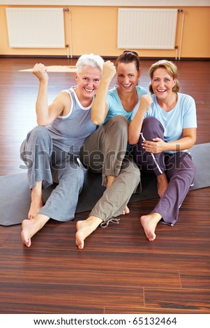 Three happy women sitting in a gym - stock photo