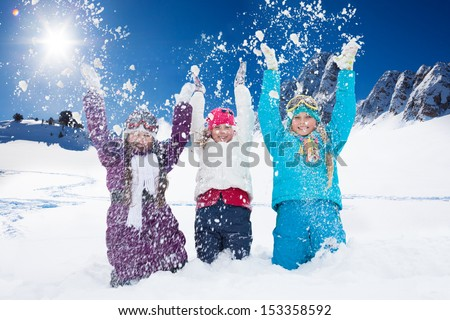 Three happy 10 years old girls throwing snow in the air at once - stock photo