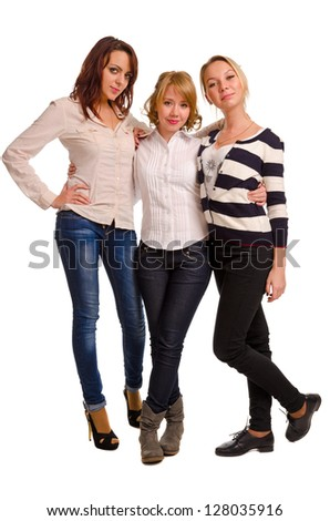 Three happy young female companions standing arm in arm in trendy casual clothes smiling at the camera isolated on white - stock photo