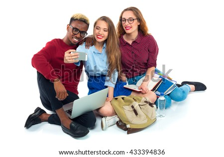 Three happy young teenager students with books, laptop, bags and makes selfie on white background
