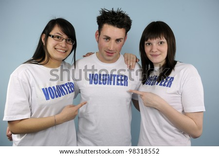 three happy young volunteers on blue background