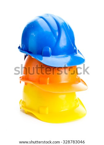 Three hard hats in blue, orange and yellow colors piled up shot on white background - stock photo