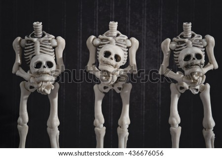 Three headless skeletons holding their heads - stock photo