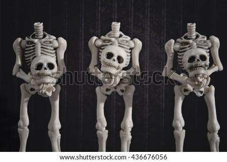 Three headless skeletons holding their heads - stock photo