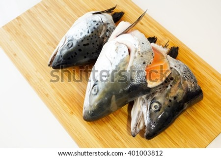 Three heads of salmon fish on a wooden cutting board ,isolated on white background