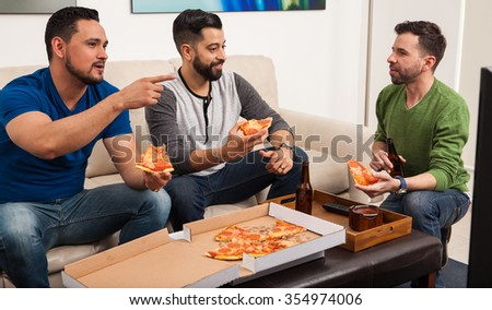 Three Hispanic male friends watching TV at home while eating pizza and drinking some beer - stock photo