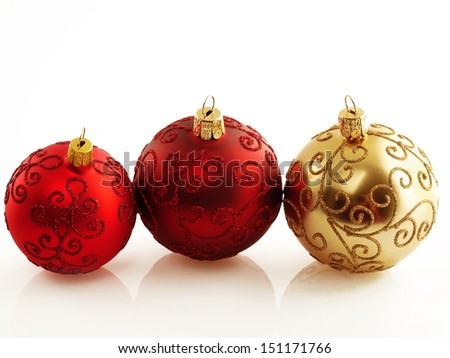 Three Holiday baubles in red and gold with soft reflection