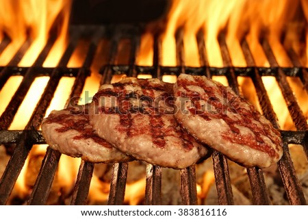 Three Homemade Browned Burgers On The Hot Flaming BBQ Charcoal Grill, Bright Flames On The Black Background, Top  View, Cookout Food For Outdoor Party Or Picnic