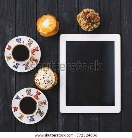 three homemade muffins, two cups of coffee and a tablet on black wooden background - stock photo