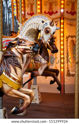 three horses run on the French carousel in the park - stock photo
