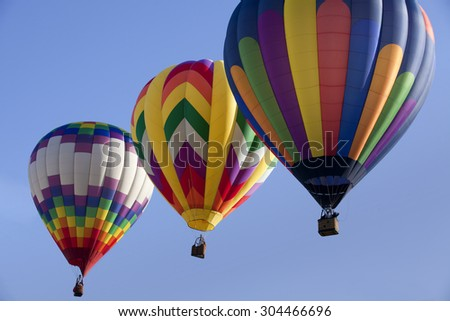 Three hot air balloons as part of the mass ascension launch of over 100 colorful balloons at  Ballooning Festival - stock photo