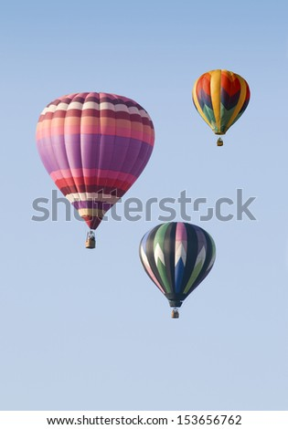 Three hot-air balloons floating against a blue sky - stock photo
