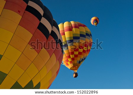 Three hot air balloons just after lift off.  Set against a deep blue sky.  - stock photo