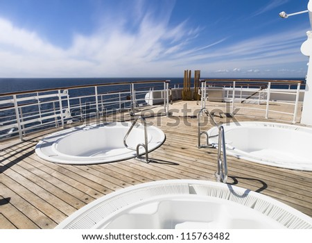 Three hot tub on the deck of a cruise in a sunny day - stock photo