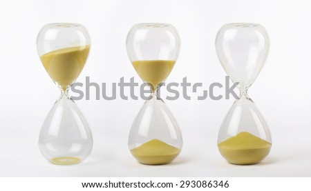 three hourglasses with yellow sand: from start to the end on white background - stock photo
