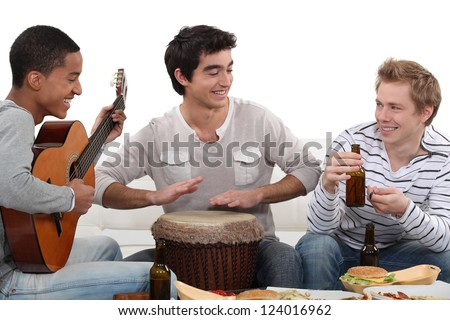 Three house-mates eating burgers and playing music - stock photo