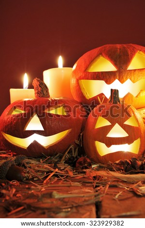 three illuminated halloween pumpkins and straw on old weathered wooden board in front of red background in candlelight - stock photo