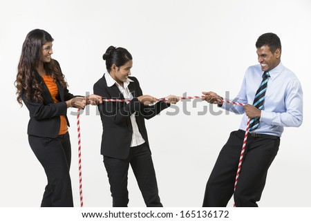 Three Indian business people playing tug war. Isolated on white background - stock photo