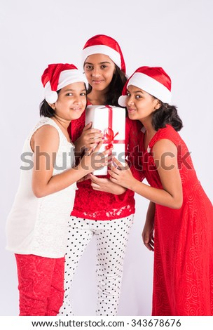 three indian girls with red cloths and santa hat holding gifts, isolated on white, asian teenage girls and christmas, standing - stock photo