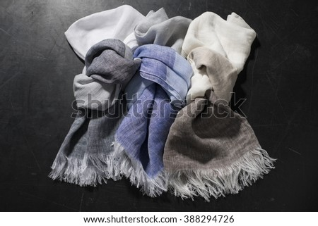 Three individually knotted fringed hand towels of various colors.