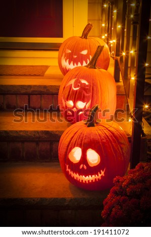 Three jack-o-lanterns sit on a porch for Halloween featuring characters from the Nightmare Before Christmas and the Monster High skeleton. - stock photo