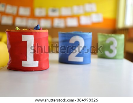 Three jars colored Red Green and blue with written one two and three in the kindergarten classroom - stock photo