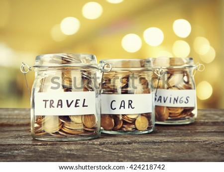 Three jars for different needs full of coins on bright background - stock photo