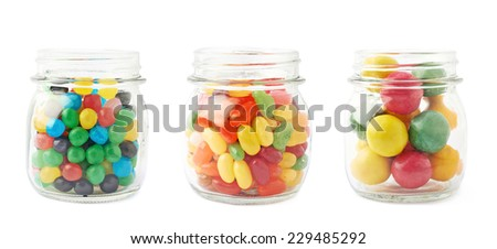 Three jars full of different kinds of candies, such as jelly beans, chewing gums and candy balls, isolated over the white background