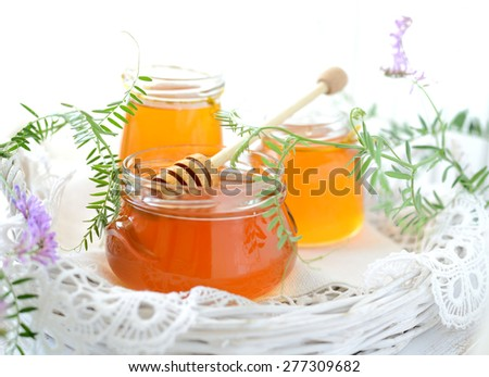 Three jars full of honey and wildflowers