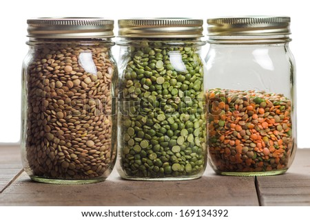 Three jars of different lentils of different colors on a counter - stock photo
