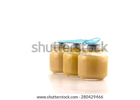 Three jars of fruit puree with a plastic spoon on a white background - stock photo
