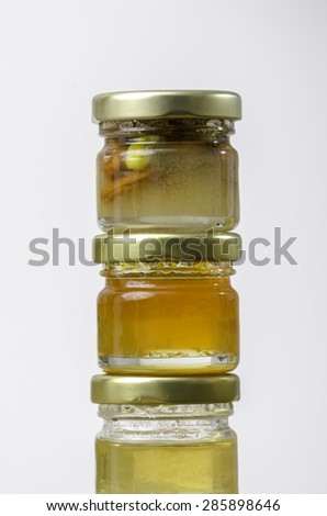 Three jars of honey of different flavors: lemon, orange, dried fruit and nuts.  - stock photo
