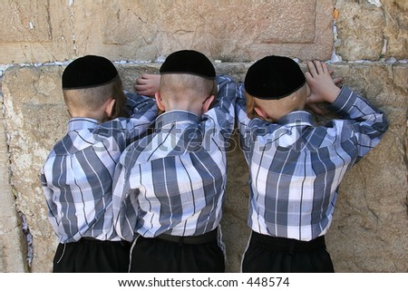 Three Jewish brothers praying at the wailing wall. - stock photo