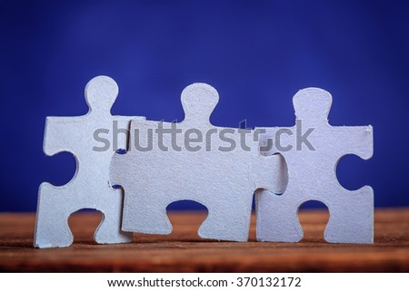 Three jigsaw puzzle pieces on a table joint together over blue background. Shallow depth of field - stock photo