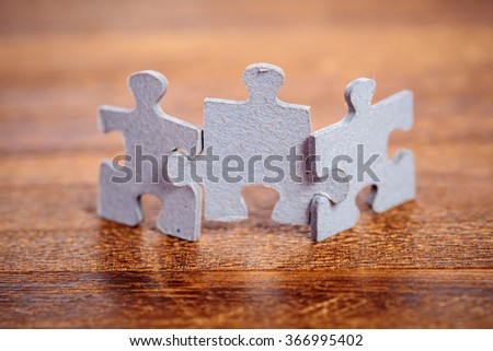 Three jigsaw puzzle pieces on a table joint together. Shallow depth of field - stock photo