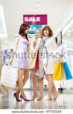 Three joyful elegant girlfriends to the utmost on shopping