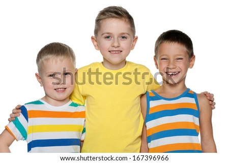 Three joyful young boys are standing together on the white background